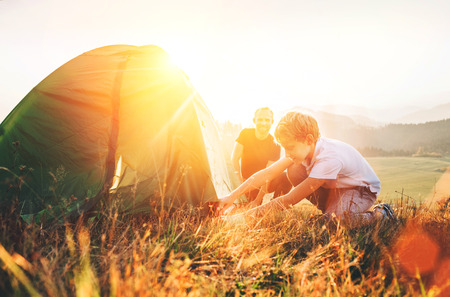 Father learn his son set up camping tent on sunset forest glade