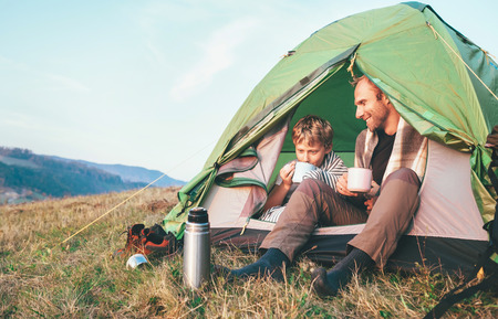 Father with son drink hot tea sitting in camp tent