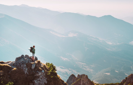 Mountain hiker with backpack tiny figurine stay on mountain peak with breathtaking hills panorama Stock Photo