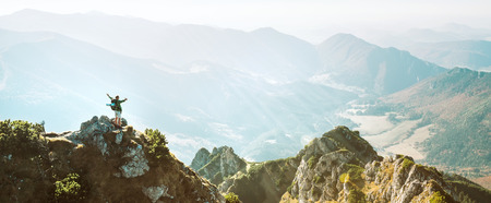 Mountain hiker with backpack tiny figurine stands on mountain peak with beautiful panorama Stock Photo
