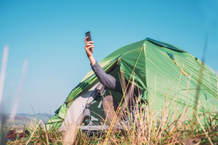 Traveler sits in touristic tent and try to catch cellular network Imagens - 110110082