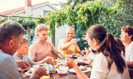 Big family have a dinner on open air in summer garden Stock Photo