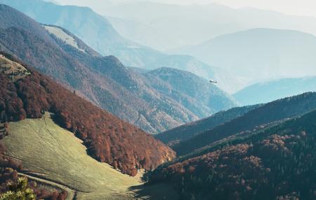 Tiny retro plane fly over the mountain hills Stock Photo