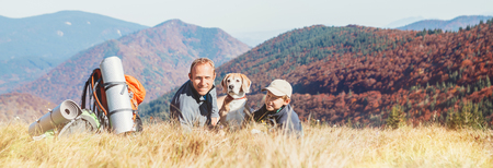 Father and son backpackers hikers rest on mountain hill with their beagle dog Фото со стока