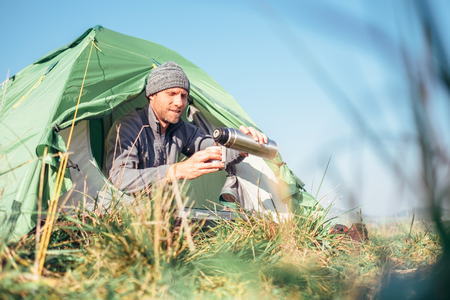 Man sits in tent and drinks hot tea