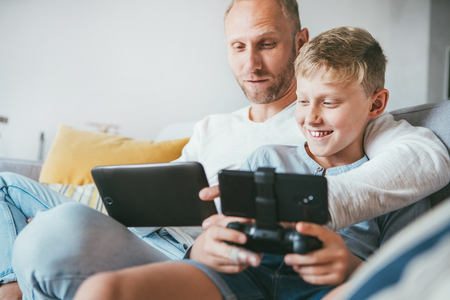 Father and son game players funs sit together using the tablet and gamepad at home on cozy sofa