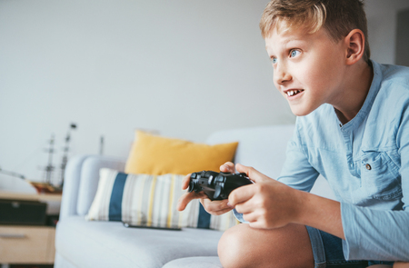 Teenager boy enthusiastically plays the game console Banque d'images - 110717088