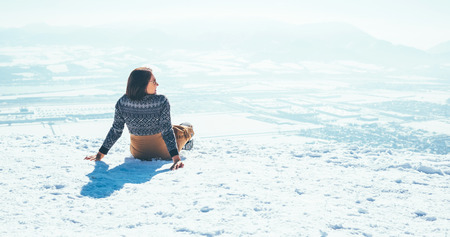 Woman sits on the snowy mountain hill over the city.
