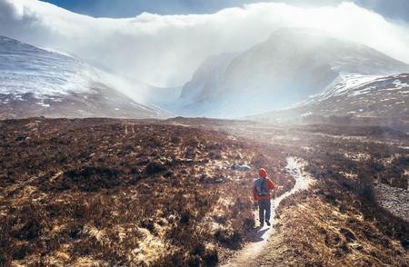 Incredibile vista sul monte Ben Nevis - è la montagna più alta delle isole britanniche. Viaggiatore da solo cammina sulla brughiera nelle Highlands, Scozia, UK