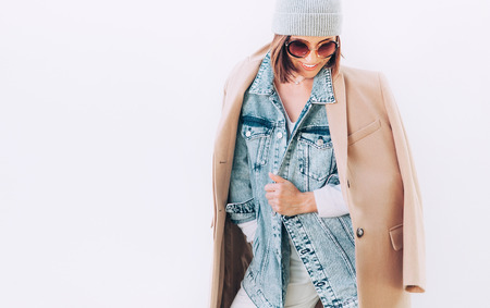 Woman in multilayered autumn outfit: camel coat, denim jacket and cashmere sweater