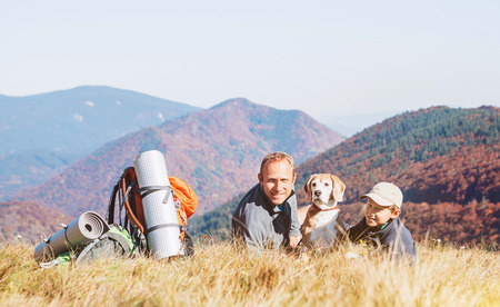 Two backpackers Father and son  hikers rest on mountain hill with their beagle dog Stock Photo