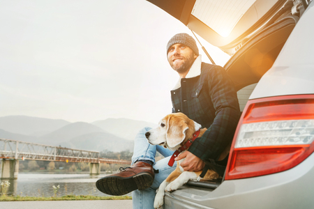 Man with beagle dog siting together in car trunk. Late autumn time