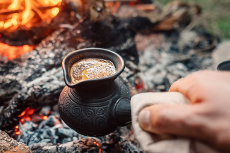 Boiling coffee in turkish cezva on campfire coals. Luxury camping concept.
