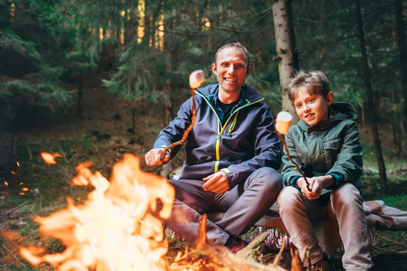 Father and son roast marshmallow candies on campfire in forest. Family relationship concept image