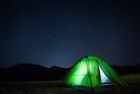 Camping tent with light inside is on the mountain valley under night starry sky 免版税图像