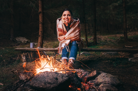 Pretty smiling young woman sits near the campfire in twilight autumn forest 스톡 콘텐츠