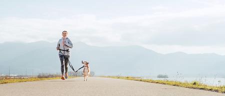 Helle, sonnige Canicross-Übungen am Morgen. Frau läuft mit seinem Beagle-Hund und glücklichem Lächeln.