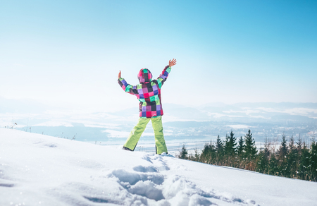 Happy little girl jumping on the deep snow hill with a great over city view