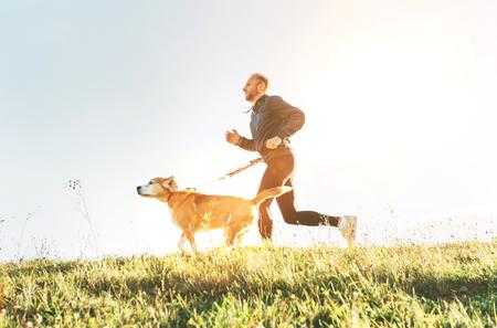 Man runs with his beagle dog. Standard-Bild - 114529901