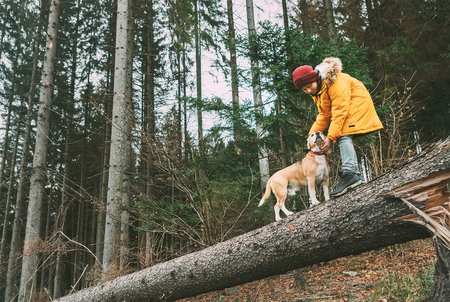 Boy in bright yellow parka walks with his beagle dog in pine forest on the falling tree