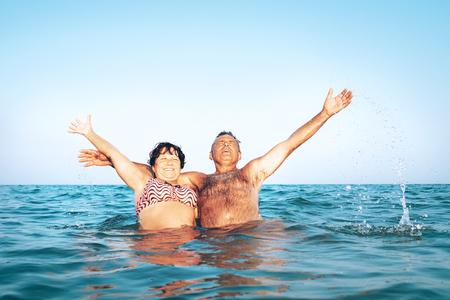 A happy caucasian senior couple enjoys their sea vacation on the beach
