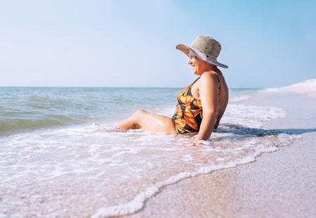Senior woman enjoy beach vacation sitting on the sea surfline