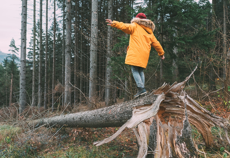 Boy in bright yellow puffer jacket walks in pine forest balancing on the falling tree. Фото со стока