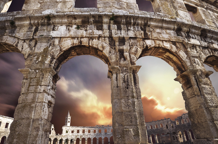 Famous Croatian city Pula old amphitheater arches with sunset sky