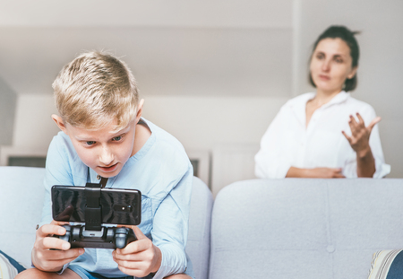 Mother unhappy with teenager son who spent his free time with electronic devices and games. Foto de archivo - 114529711