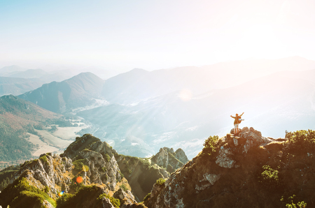 Mountain hiker with backpack tiny figurine stands on highest mountain peak with beautiful panorama. Stock Photo