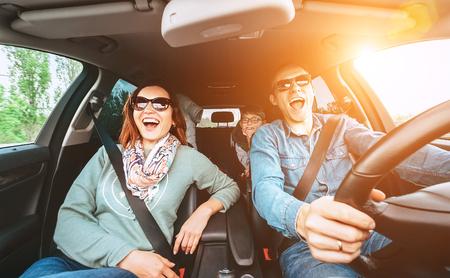 Fröhliche junge traditionelle Familie hat eine lange Autofahrt und singt laut das Lieblingslied zusammen.