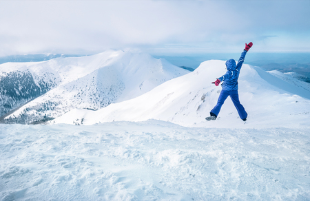 Wide angle shot of woman dressed in ski warm clothing jumping on the mountain peak with snowy range and valley 写真素材