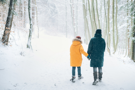 Mother and son walking in snowy forest. Mother and son relatives concept image. Фото со стока