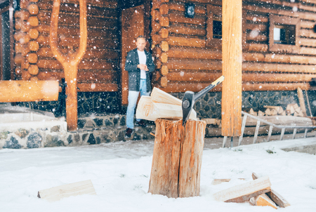 Man staying in the country house porch. Wooden stump with axe on snowy yard unfocused with heavy snowflakes . Winter countryside holidays concept image