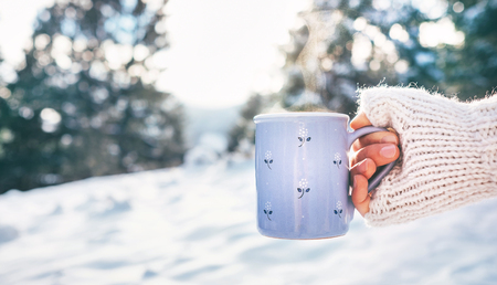 Woman take in hand cup of hot drink. Winter forest glade, bright sunnyday scene Stock Photo