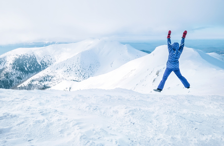 Wide angle shot of woman dressed in ski warm clothing jumping on the mountain peak with snowy range and valley on the background. Freedom concept image.  写真素材