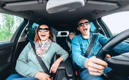 Fröhliche junge traditionelle Familie hat eine lange Autofahrt und singt laut das Lieblingslied zusammen. Sicherheitsreitautokonzept Weitwinkel im Autoansichtsbild.