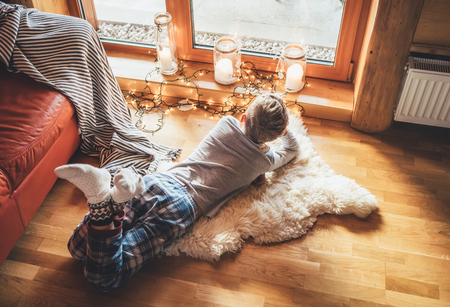 Boy lying on floor on sheepskin and looking in window in cozy home atmosphere. Peaceful moments of cozy home concept image. Stockfoto