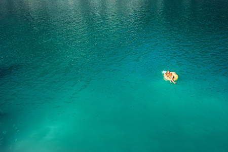 Woman swimming on inflatable pineapple ring in mountain lake top aerial view. Carefree vacation lifetime concept image.