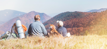 Father and son travelers with their beagle dog sit together in mountain valley with beautiful hills view. Trekking with kids and pets concept image.