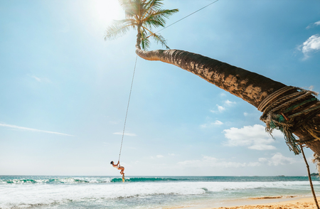 Woman in white swimsuit swinging on tropical palm swing over the ocean waves. Careful summer tropic climate countries vacation concept image. Stock Photo