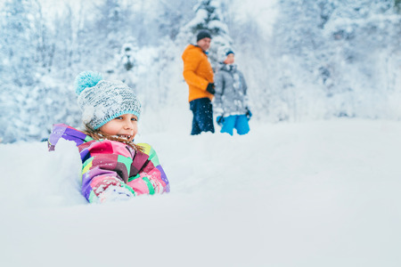 Happy smiling little girl sitting in deep snow when she walking with family in winter snowy forest