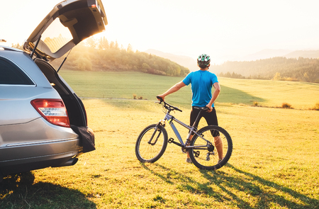 Man with bMan came by auto in mountain with his bicycle on the roof. Mountain biking concept image