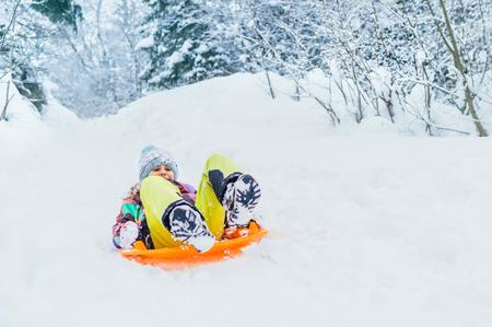 Little girl slide down from snow slope sitting in one slide.