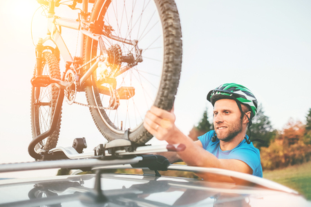 Cyclist man hold on  his bike on the car roof
