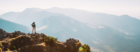 Mountain hiker with backpack tiny figurine stay on mountain peak with beautiful panorama Stock Photo