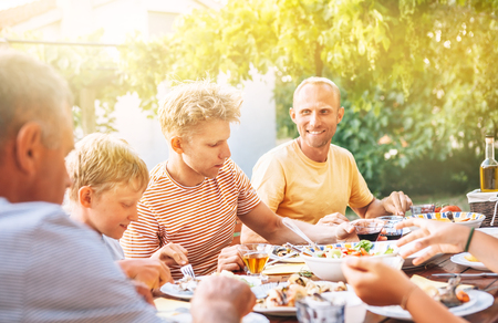 Family have a dinner on open air in summer garden