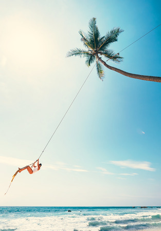 Woman dangles on tropical palm tree swing over ocean waves