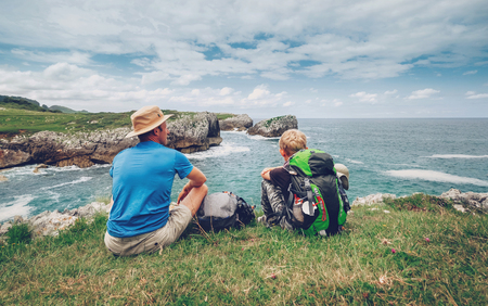 Father and son backpackers rest on the rocky sea side Stock Photo