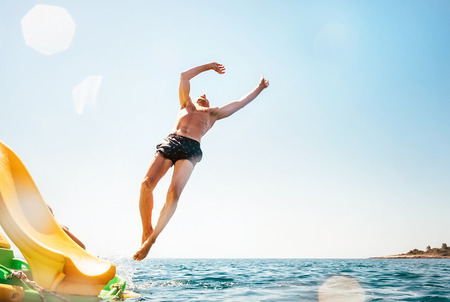 Man jumping backwards somersault into the sea. Happy beach vacation concept image. Stockfoto